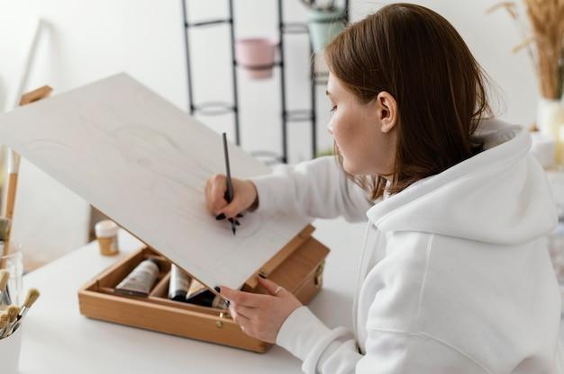 Mulher jovem desenhando em uma tela