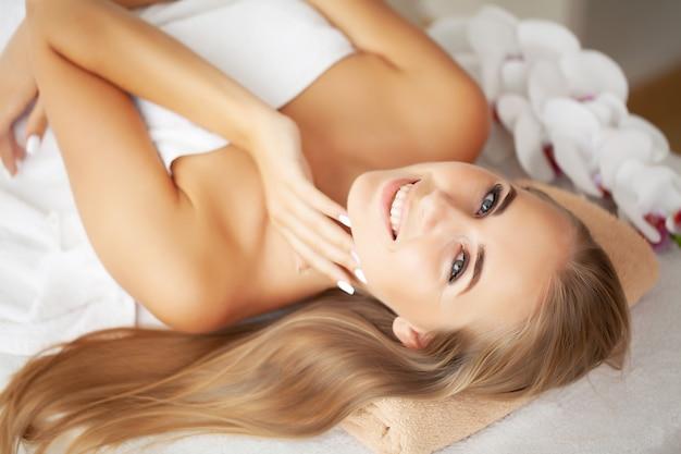 Mulher jovem, desfrutando de massagem facial em salão de spa.