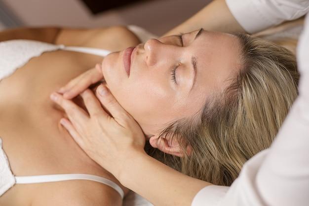Mulher jovem desfrutando de tratamento facial no salão spa
