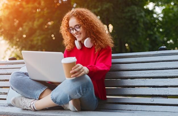 Mulher jovem desfrutando de uma bebida enquanto está sentada no banco