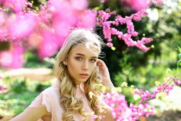 Mulher jovem desfrutar de flores no jardim. menina entra no parque em um dia ensolarado de primavera.