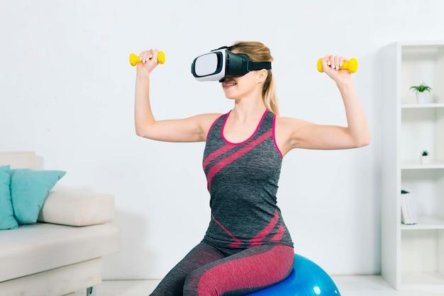 Mulher jovem, desgastar, a, realidade virtual, headset, sentando, ligado, a, esfera aptidão, exercitar, com, amarela, dumbbells