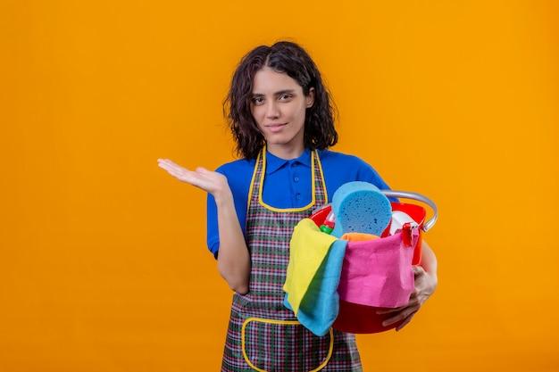Mulher jovem, desgastar avental, segurando balde, com, ferramentas limpeza, apresentando, com, braço mão, olhar confiante, sobre, parede laranja