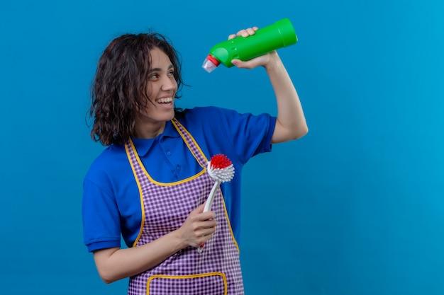 Mulher jovem, desgastar, avental, segurando, escova esfregando, e, garrafa, de, materiais limpeza, sorrindo, alegremente, olhar alegre, sobre, parede azul