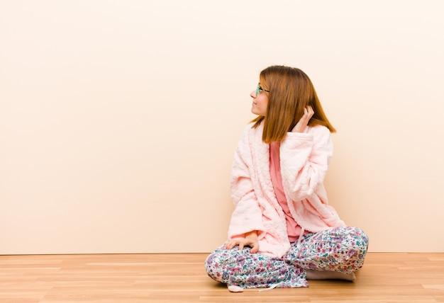 Mulher jovem, desgastar, pijama, sentando casa, sentindo-se sem noção e confuso, pensando uma solução, com a mão no quadril e outro na cabeça, vista traseira