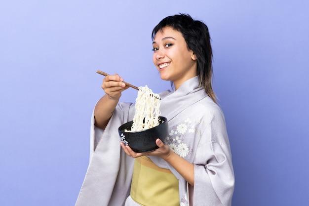 Mulher jovem, desgastar, quimono, isolado, azul, segurando, um, tigela macarrão, com, pauzinhos