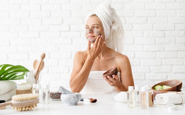 Mulher jovem, desgastar, toalhas brancas, aplicar, spa, argila, máscara facial, ligado, dela, rosto