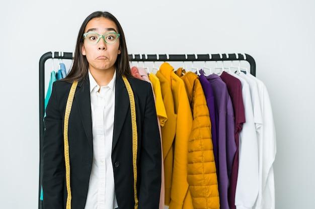 Mulher jovem designer asiática isolada na parede branca encolhe os ombros e abre os olhos confusa
