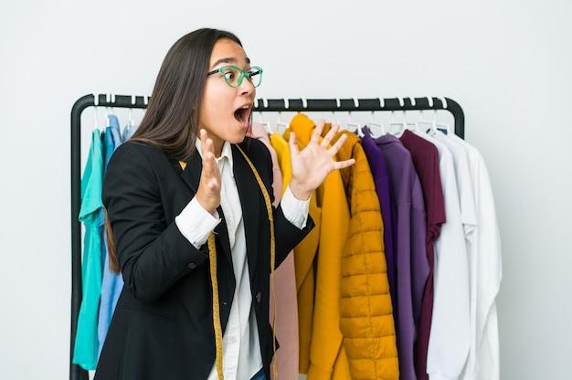 Mulher jovem designer asiática isolada no fundo branco grita alto, mantém os olhos abertos e as mãos tensas.
