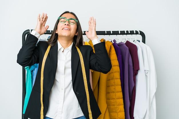 Mulher jovem designer asiática isolada no fundo branco, gritando para o céu, olhando para cima, frustrada.