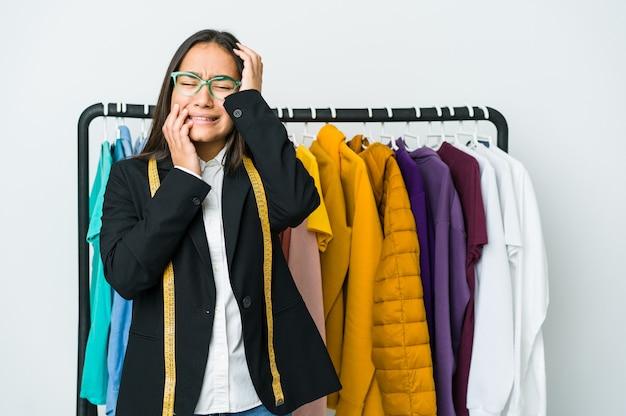 Mulher jovem designer asiático choramingando e chorando desconsoladamente.