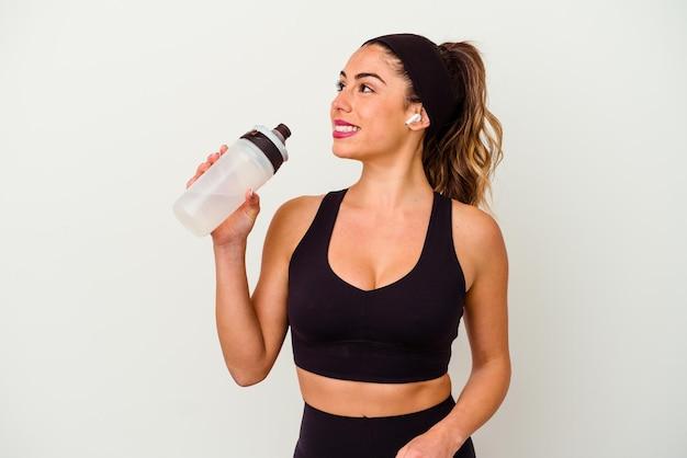 Mulher jovem desportiva bebendo água de uma garrafa isolada no branco