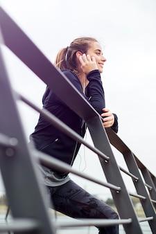 Mulher jovem desportiva com fones de ouvido, apoiando-se na vedação e olhando para longe ao ar livre