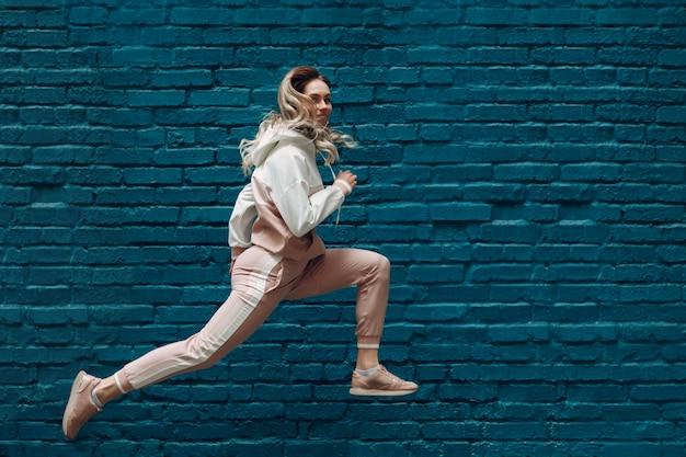Mulher jovem desportiva em um terno de esportes-de-rosa. pulando e correndo feminino.