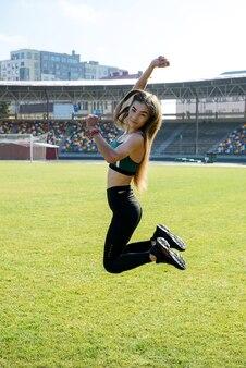 Mulher jovem desportiva fazendo agachamento de aquecimento, alongamento no estádio. conceito de estilo de vida saudável