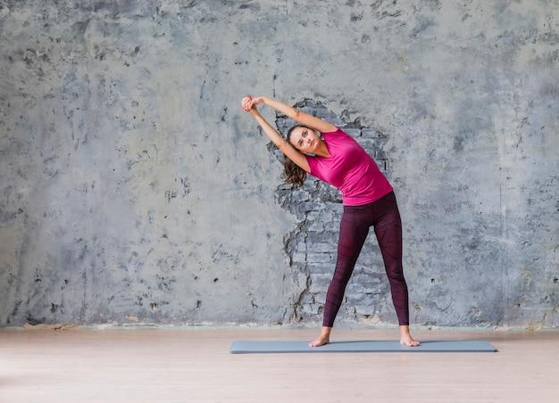 Mulher jovem desportiva fazendo exercício fitness em pé contra a parede cinza