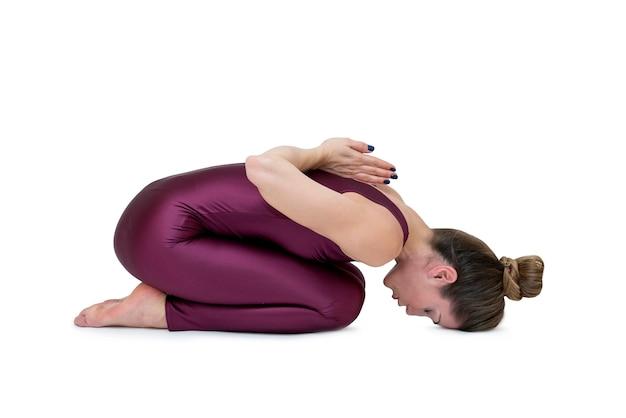 Mulher jovem desportiva fazendo pose de balasana pratica yoga