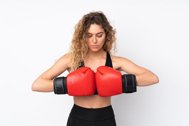 Mulher jovem desportiva isolada na parede branca com luvas de boxe
