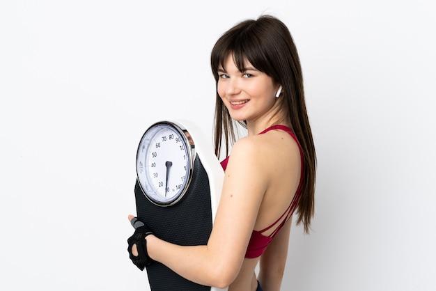 Mulher jovem desportiva isolada no branco com balança