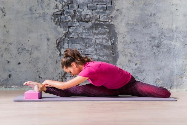 Mulher jovem desportiva no sportswear, apoiando-se no bloco de madeira contra o muro de concreto de tijolo