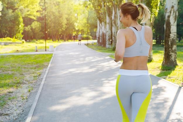Mulher jovem desportiva no sportswear correndo no parque de manhã