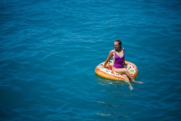 Mulher jovem despreocupada, desfrutando de um dia relaxante no mar, flutuando em um anel inflável, vista superior. conceito de férias do mar. foco seletivo