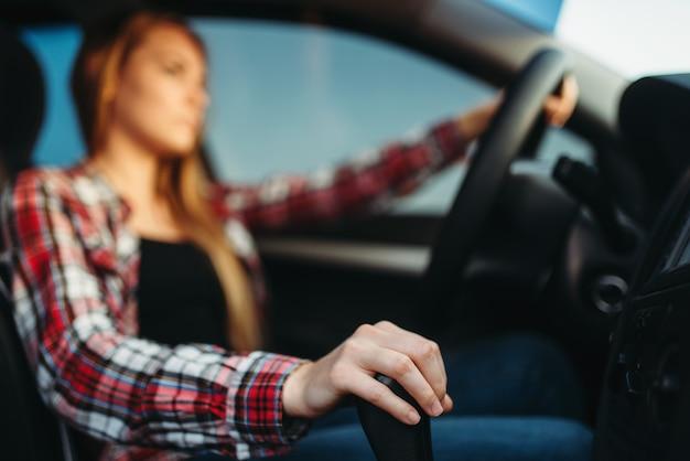 Mulher jovem dirige um carro