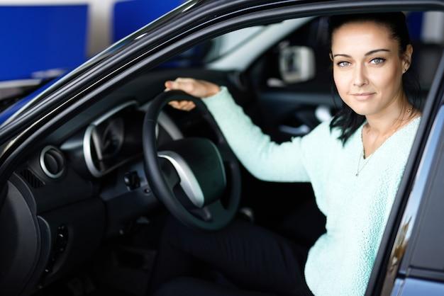 Mulher jovem dirigindo carro em concessionária