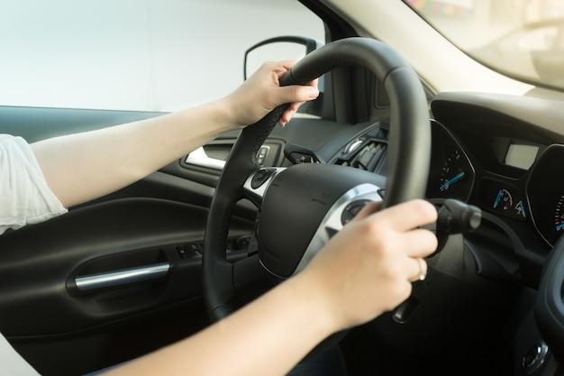 Mulher jovem dirigindo um carro e segurando o volante de mãos dadas