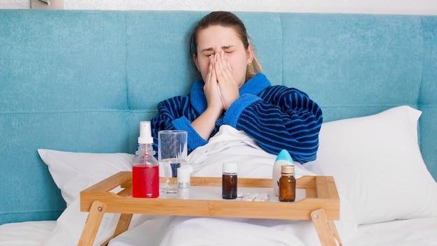 Mulher jovem doente com resfriado deitada na cama com muitos medicamentos e pílulas.