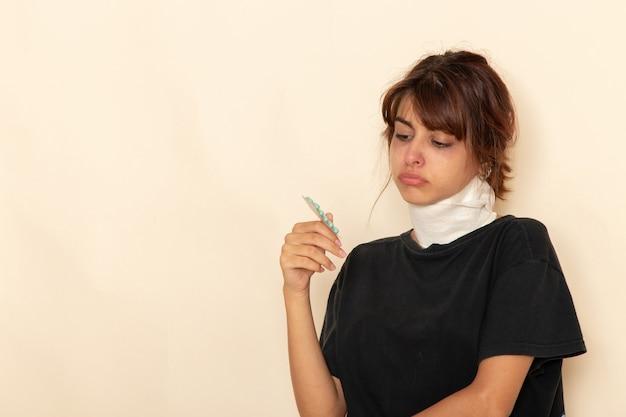 Mulher jovem doente de frente com alta temperatura e se sentindo mal segurando comprimidos na superfície branca