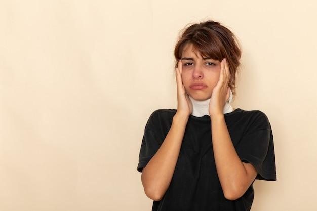 Mulher jovem doente de vista frontal com alta temperatura cobrindo a garganta e se sentindo mal na superfície branca