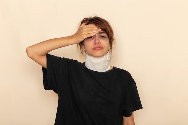 Mulher jovem doente de vista frontal com alta temperatura cobrindo a garganta, sentindo-se doente em uma superfície branca