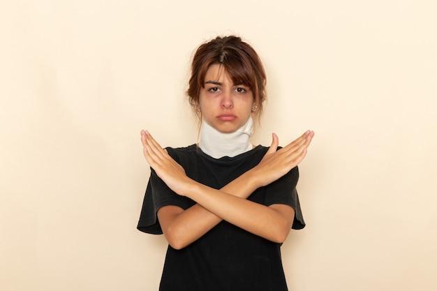 Mulher jovem doente de vista frontal com alta temperatura e se sentindo mal, cruzando os braços na superfície branca