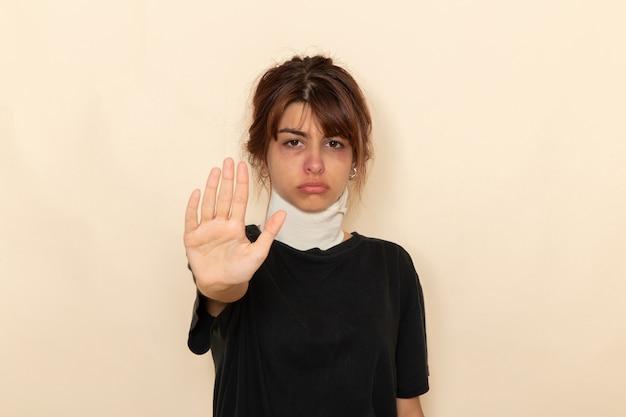 Mulher jovem doente de vista frontal com alta temperatura e se sentindo mal, mostrando o sinal de pare na superfície branca