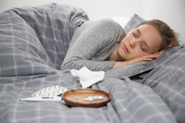 Mulher jovem doente deitada na cama, dormindo