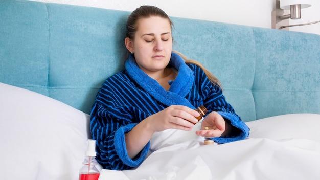 Mulher jovem doente deitada na cama e segurando os comprimidos por lado.
