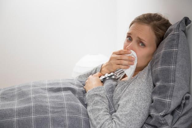 Mulher jovem doente na cama espirros, segurando pílulas na mão
