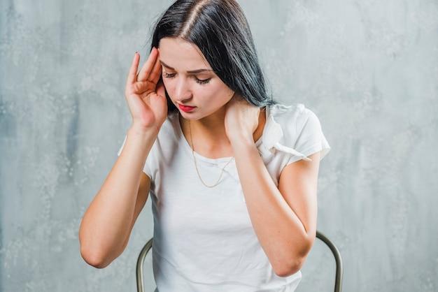 Mulher jovem doente sentado contra o pano de fundo cinzento, sofrendo de dor de cabeça