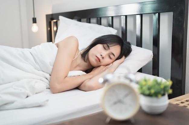 Mulher jovem dormindo e despertador no quarto de casa