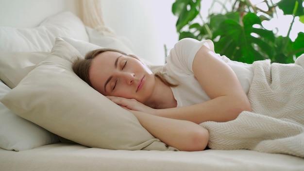 Mulher jovem dormindo em um travesseiro branco na cama mulher dormindo pacificamente na cama
