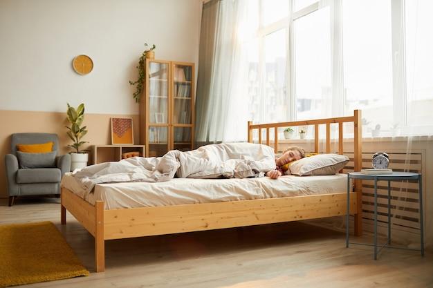 Mulher jovem dormindo na cama de manhã em um quarto moderno