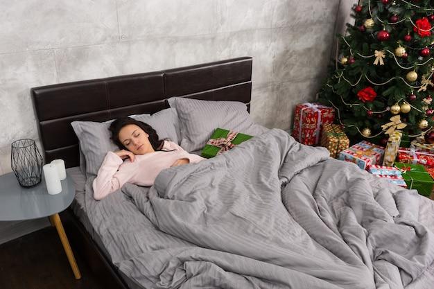 Mulher jovem dormindo na cama de pijama e presente de natal, deitada perto do quarto, em estilo loft, com árvore de natal e muitos presentes