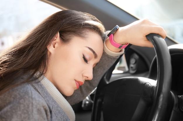 Mulher jovem dormindo no carro durante um engarrafamento