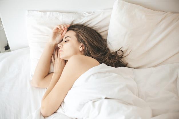 Mulher jovem dormindo pacificamente no quarto com lençóis brancos frescos, olhos fechados.