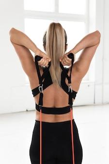Mulher jovem durante o treino com elásticos de resistência no ginásio. exercício de extensão aérea de tríceps.