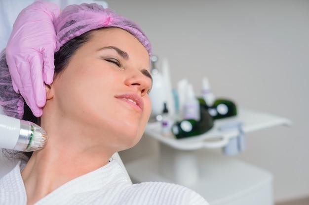 Mulher jovem durante um tratamento facial com ferramenta profissional no centro médico