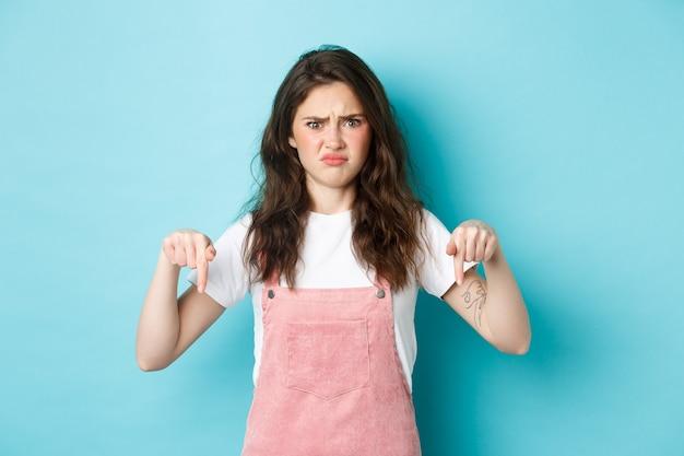 Mulher jovem duvidosa franzindo a testa e se encolhendo de algo ruim, apontando o dedo para uma coisa estranha, tendo hesitações, fundo azul.