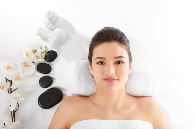 Mulher jovem e acessórios de spa em branco, vista superior