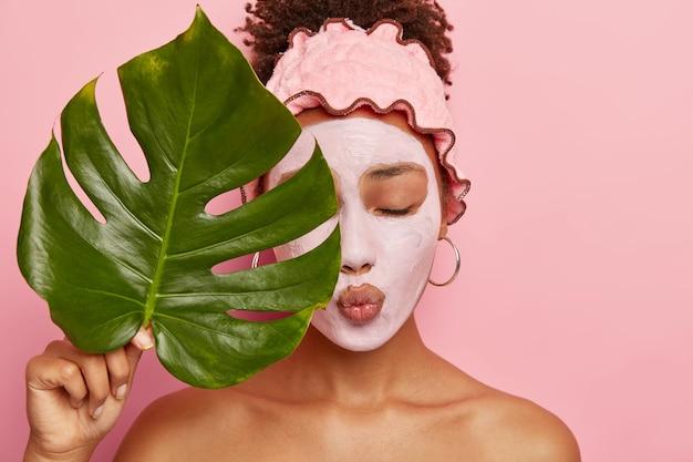 Mulher jovem e adorável afro aplica máscara nutritiva de argila, tem os olhos fechados, lábios dobrados, cobre metade do rosto com uma grande folha verde, usa uma faixa de chuveiro, isolada na parede rosa